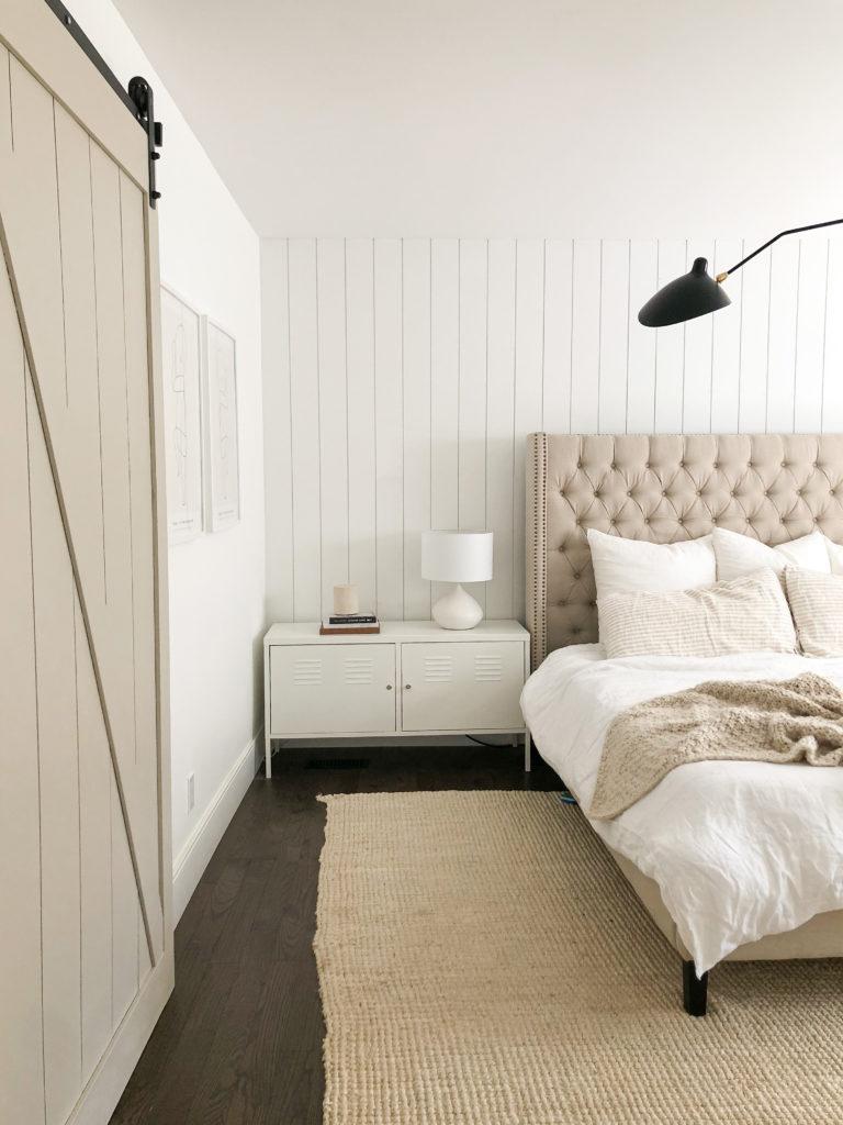 Sliding barn door in bedroom with white and beige accessories.