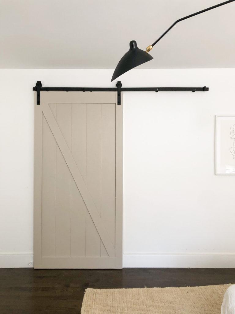 Beige sliding barn door with black hardware on a white door.