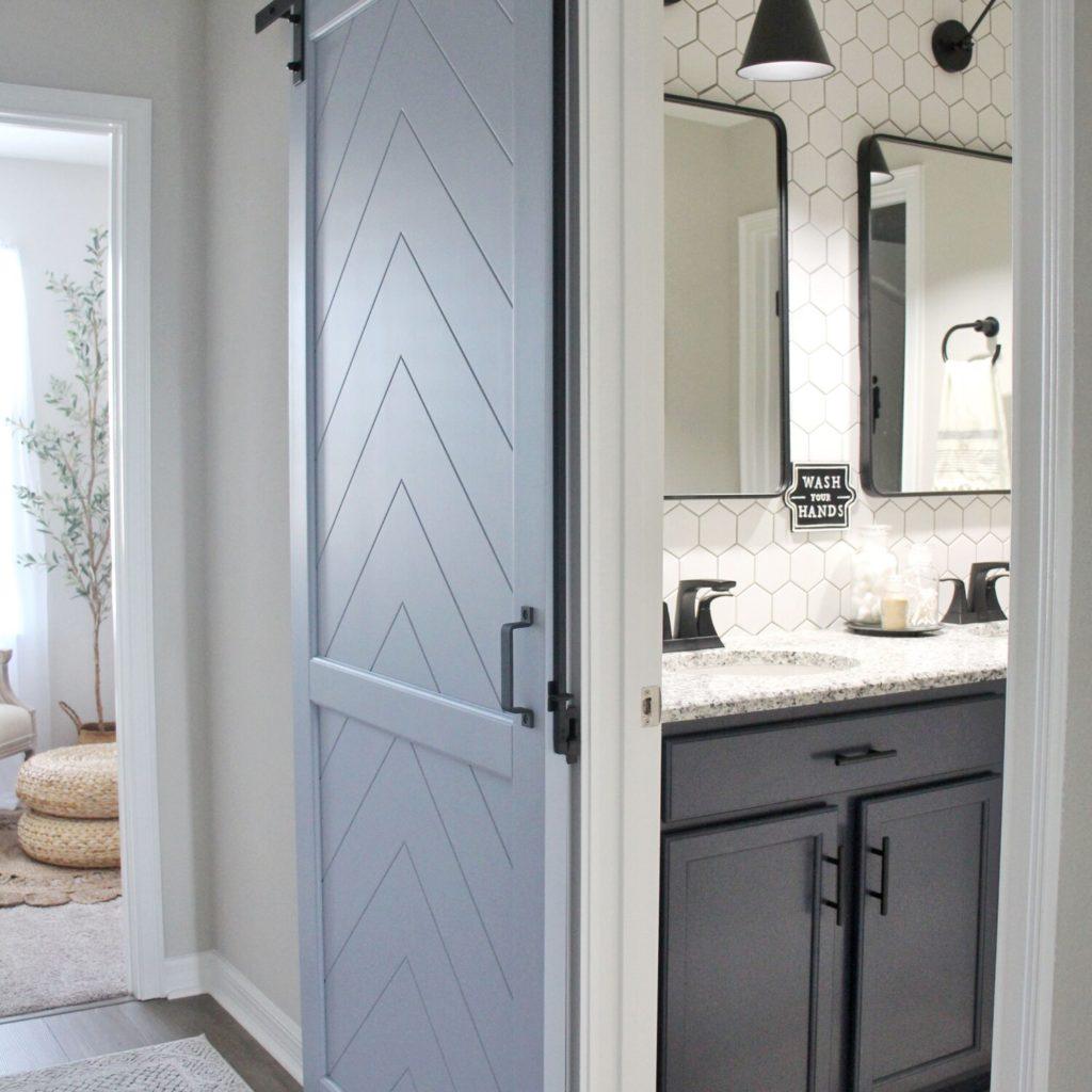 Modern concept washroom with sink and a sliding grey barn door.