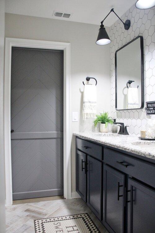 View of grey bathroom barn door with a black lock from inside the bathroom.