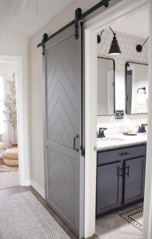 Grey herringbone barn door with a barn door lock leading into a modern white bathroom.