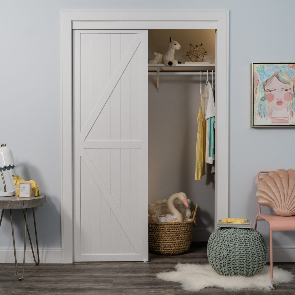 White K Design Bypass Closet Door in a childrens room with pastel toys in closet.