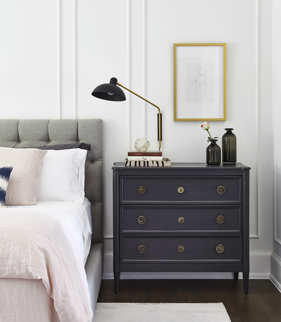 Black three drawer side table next to grey bed in a modern bedroom.