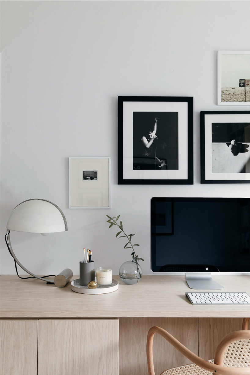 Office with a large computer screen and black and white photos hanging on wall above desk.