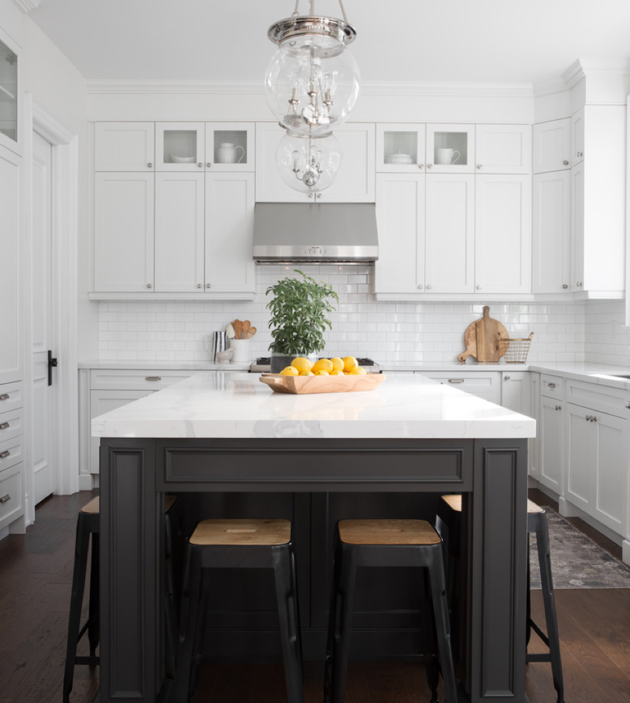 All white modern kitchen with a black centre island with black stools.