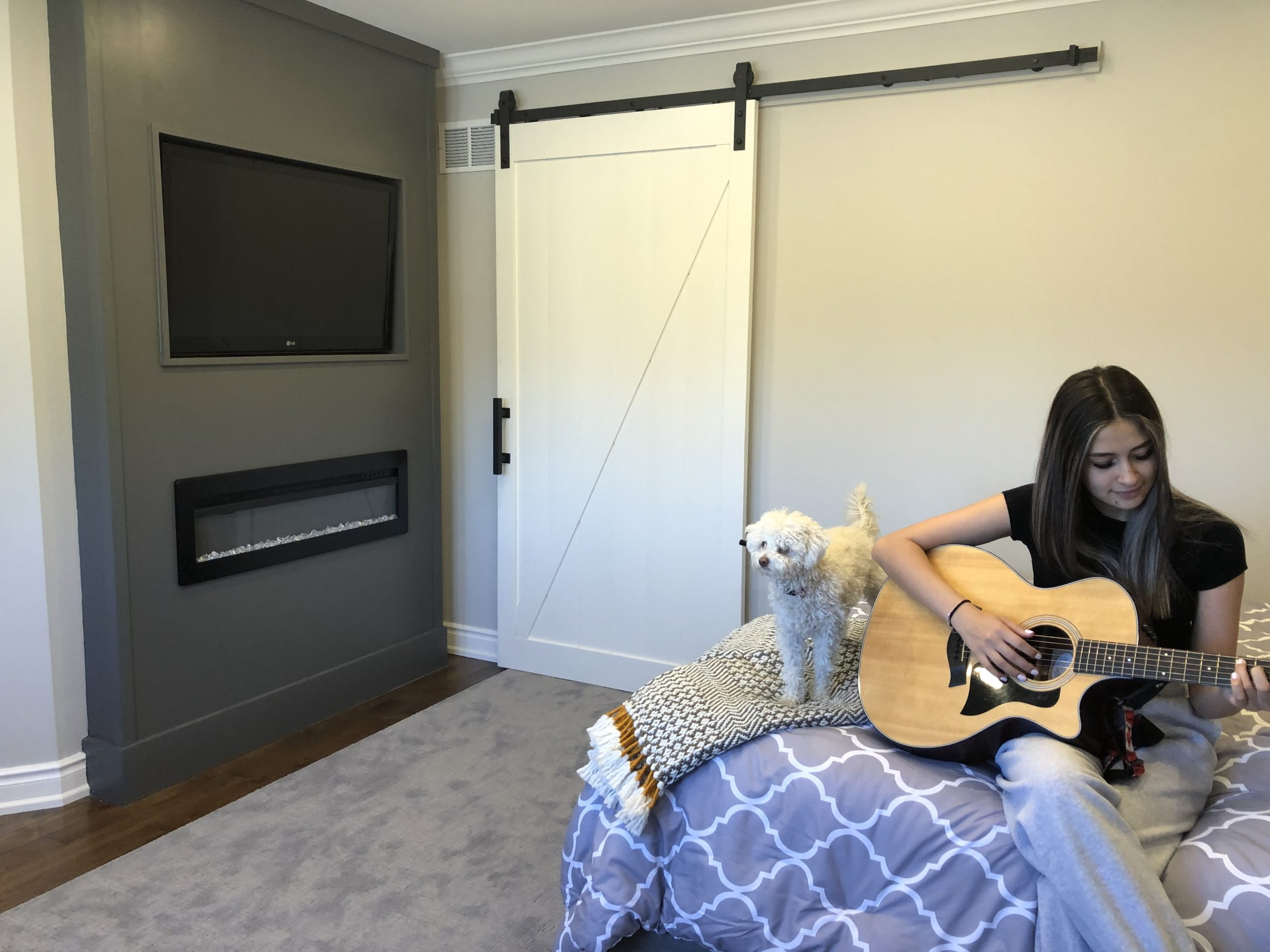 White Barn Door behind teen girl sitting with a small white dog playing guitar on her bed.